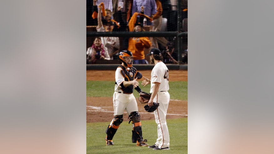 San Francisco Giants' Buster Posey and Madison Bumgarner smile and shake hands after the Giants beat the Royals 5-0 during Game 5 of baseball's World Series Sunday, Oct. 26, 2014, in San Francisco. The Giants beat the Royals 5-0 to lead the series 3-2. (AP Photo/Charlie Riedel)