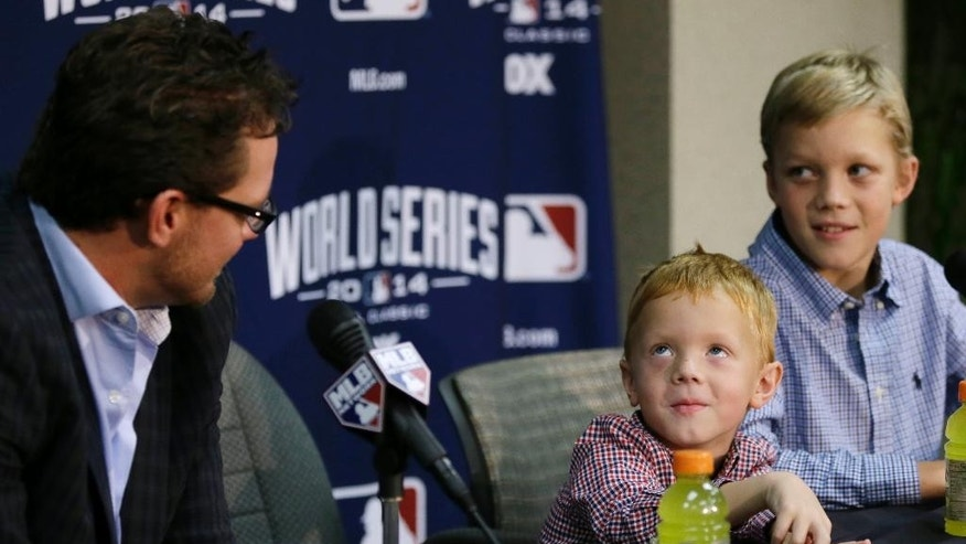 San Francisco Giants pitcher Jake Peavy, left, watches as his son Judson, center, and Wyatt, right, respond to a question about who their favorite player is during a news conference, Monday, Oct. 27, 2014, in Kansas City, Mo. The Giants are scheduled to play the Kansas City Royals in Game 6 of the baseball World Series in Kansas City on Tuesday. (AP Photo/Charlie Neibergall)
