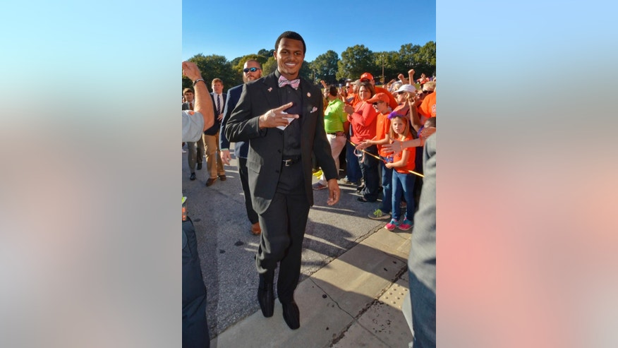 Clemson quarterback Deshaun Watson flashes the peace sign with his injured hand during Tiger Walk before the start of an NCAA college football game against  Syracuse in Clemson, S.C.,  Saturday, Oct. 25, 2014. (AP Photo/ Richard Shiro)