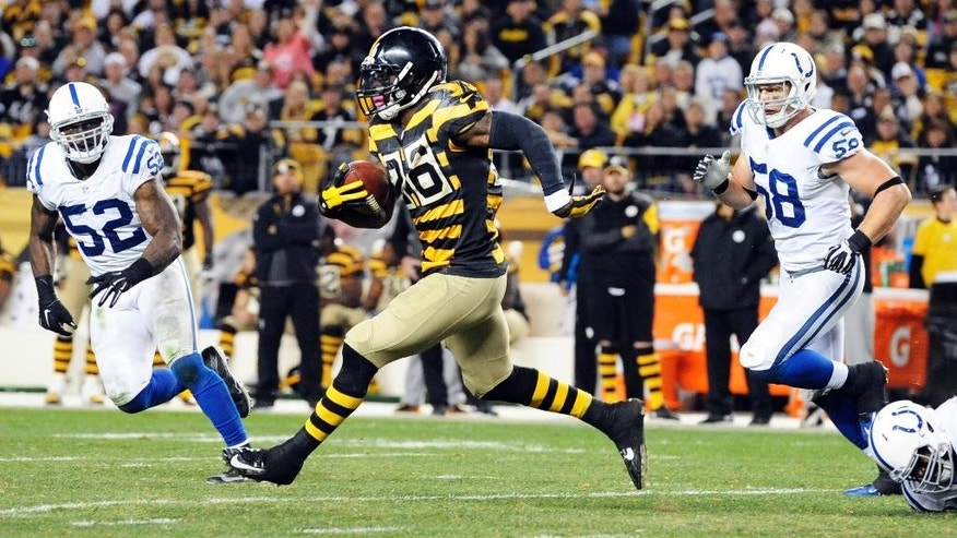 Pittsburgh Steelers running back Le'Veon Bell (26) runs away from Indianapolis Colts linebackers Andy Studebaker (58) and D'Qwell Jackson in the third quarter of the NFL football game, Sunday, Oct. 26, 2014, in Pittsburgh. (AP Photo/Don Wright)