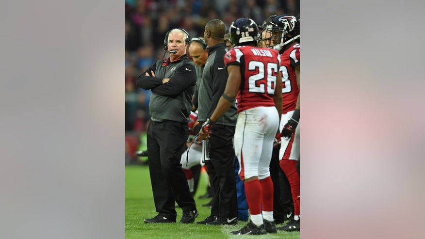 Atlanta Falcons head coach Mike Smith, left, stands on the touchline during the NFL football game against Detroit Lions at Wembley Stadium, London, Sunday, Oct. 26, 2014.  (AP Photo/Tim Ireland)