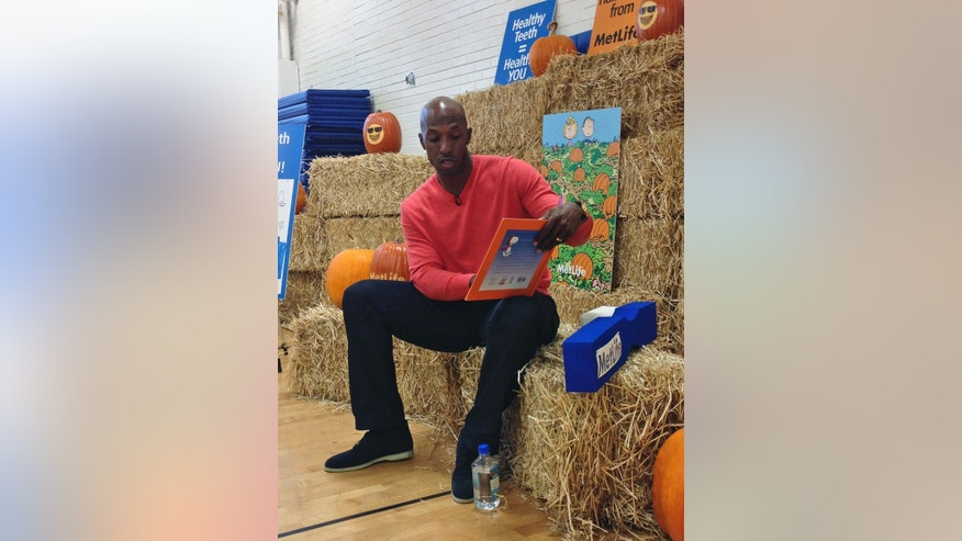 "Retired NBA basketball player Chauncey Billups reads ""It's the Great Pumpkin, Charlie Brown"" to students at Fairview Elementary in Denver on Monday, Oct. 27, 2014. The NBA season is about to tip off and for the first time in nearly two decades, Billups won't be taking the court. (AP Photo/Pat Graham)"