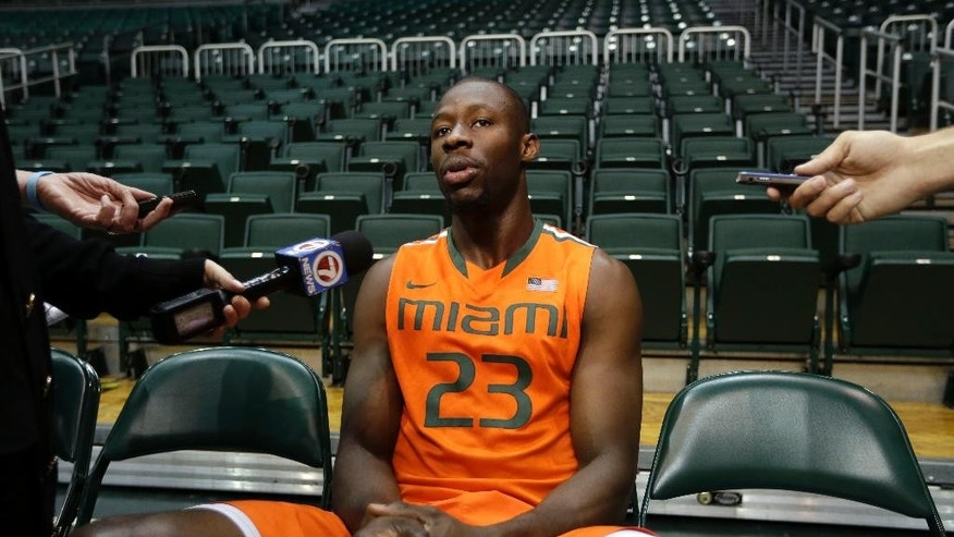In this Thursday, Oct. 16, 2014, photo, Miami's  Tonye Jekiri responds to a question during NCAA college basketball media day, in Coral Gables, Fla. Soccer is Jekiri's first love and the sport he played growing up in Nigeria. He moved to Florida in 2010 to begin a basketball career and now he's a 6-foot-11 starting center for the Miami Hurricanes. (AP Photo/Lynne Sladky)