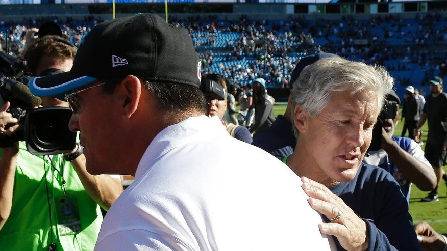 Carolina Panthers head coach Ron Rivera, left, heads back to his sideline after speaking with Seattle Seahawks head coach Pete Carroll after the second half of an NFL football game, Sunday, Oct. 26, 2014, in Charlotte. The Seattle Seahawks won 13-9. (AP Photo/Bob Leverone)