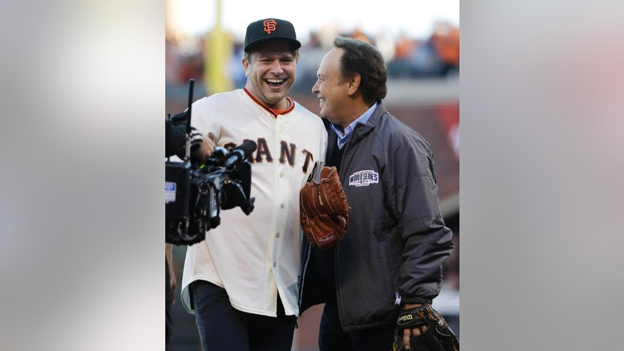 Robin Williams' son, Zak Williams, left, talks to comedian Billy Crystal after throwing out the ceremonial first pitch to Crystal before  Game 5 of baseball's World Series between the Kansas City Royals and the San Francisco Giants Sunday, Oct. 26, 2014, in San Francisco. (AP Photo/Matt Slocum)