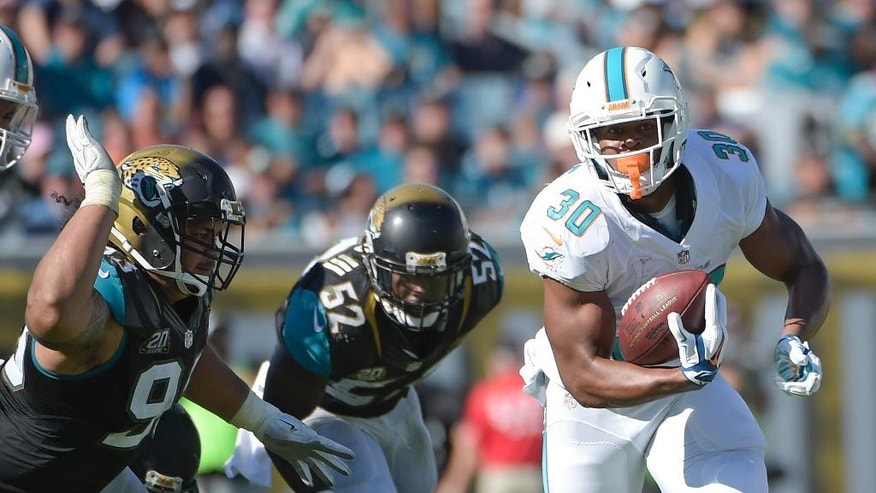 Miami Dolphins running back Daniel Thomas (30) makes a short gain as he gets by Jacksonville Jaguars defensive end Tyson Alualu, left, and outside linebacker J.T. Thomas (52) during the second half of an NFL football game in Jacksonville, Fla., Sunday, Oct. 26, 2014. (AP Photo/Phelan M. Ebenhack)