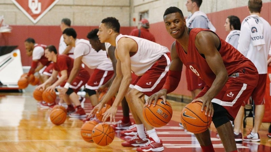 Oklahoma guard Buddy Hield, right, dribbles during an NCAA college basketball practice following media day in Norman, Okla., Monday, Oct. 27, 2014. Preseason All Big 12 pick Hield leads an Oklahoma team with high expectations. (AP Photo/Sue Ogrocki)