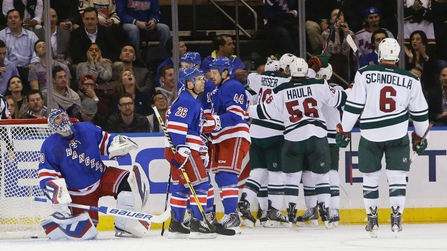 New York Rangers goalie Henrik Lundqvist (30), of Sweden, gets up as the Minnesota Wild celebrate a goal by Nate Prosser during the second period of an NHL hockey game Monday, Oct. 27, 2014, in New York.  (AP Photo/Frank Franklin II)