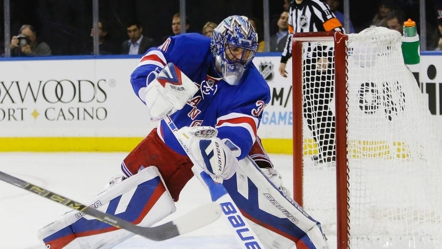 New York Rangers goalie Henrik Lundqvist (30), of Sweden, clears the puck during the first period of an NHL hockey game against the Minnesota Wild Monday, Oct. 27, 2014, in New York.  (AP Photo/Frank Franklin II)