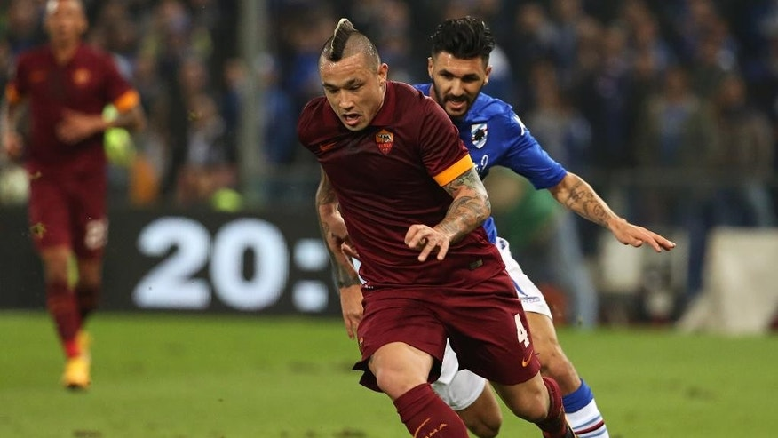 AS Roma midfielder Radja Nainggolan, left, controls the ball past Sampdoria midfielder Roberto Soriano  during a Serie A soccer match between Sampdoria and AS Roma, in Genoa, Italy, Saturday, Oct 25, 2014. (AP Photo/Carlo Baroncini)