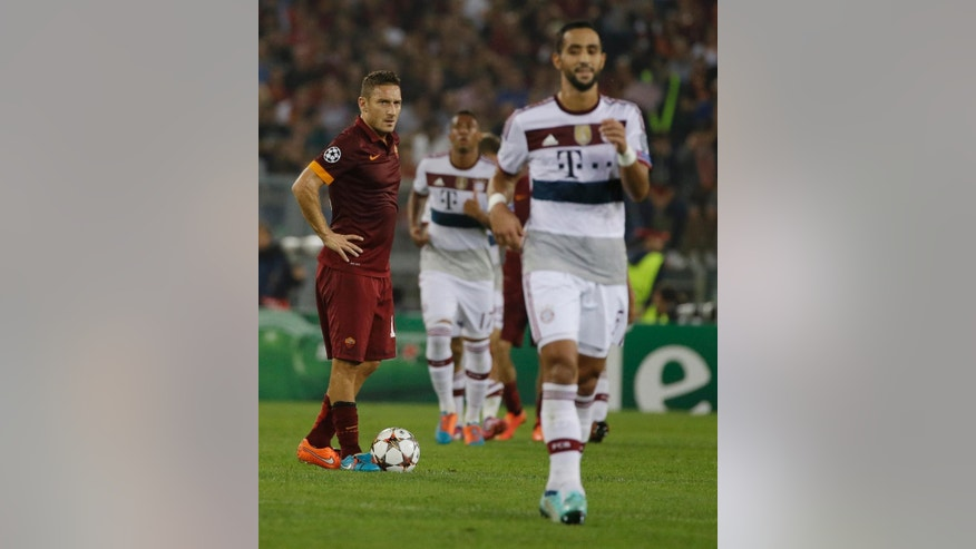 Bayern's Mehdi Benatia, right ,walks past Roma's Francesco Totti during the Group E Champions League soccer match between Roma and Bayern Munich at the Olympic stadium, in Rome, Tuesday, Oct. 21, 2014. Bayern won 7-1. (AP Photo/Alessandra Tarantino)