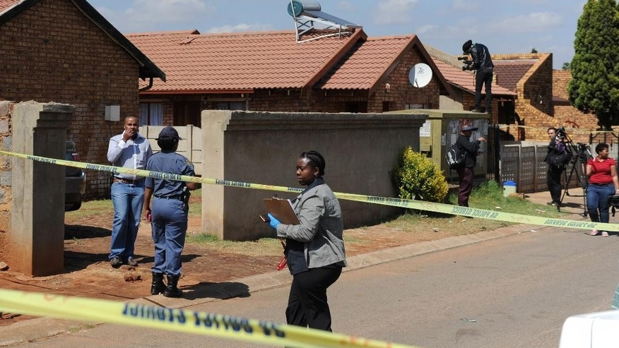 Police, forensic investigators and press  work outside the home of actress and singer, Kelly Khumalo, in Vosloorus, east of Johannesburg, Monday Oct. 27, 2014. Her boyfriend  Bafana Bafana captain Senzo Meyiwa was shot dead at her home Sunday night.  The 27-year-old national team and Orlando Pirates goalkeeper and captain, who was married, was shot dead at about 8pm in Vosloorus on Sunday. (AP Photo)