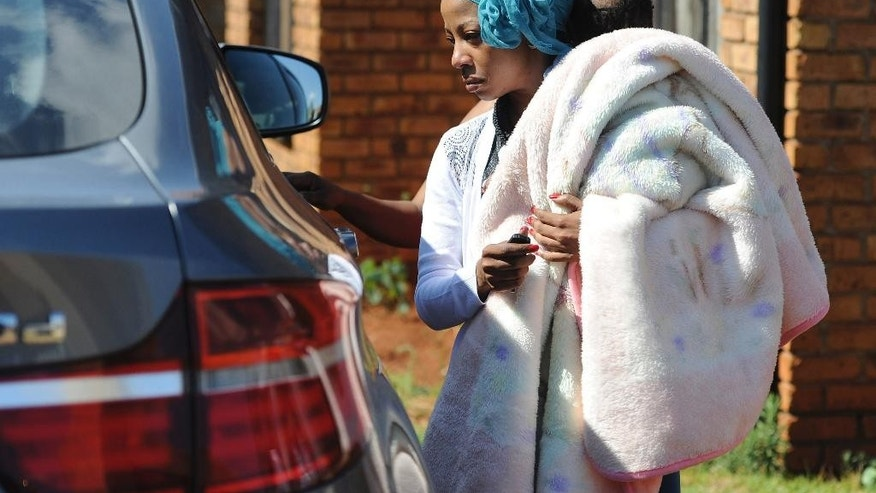 Actress and singer, Kelly Khumalo, carries her baby outside her home in Vosloorus, east of Johannesburg, Monday Oct. 27, 2014. Her boyfriend  Bafana Bafana captain Senzo Meyiwa was was fatally shot at a friend's house during an attempted robbery on Sunday night, police said. The 27-year-old Meyiwa was shot in the upper body, police spokesman Brig. Neville Malila said Monday. (AP Photo)