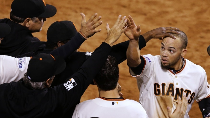 San Francisco Giants Juan Perez, right, is congratulated after hitting two-run RBI double during the eighth inning of Game 5 of baseball's World Series Sunday, Oct. 26, 2014, in San Francisco. The Giants defeated the Royals 5-0 to lead the series 3-2 games. (AP Photo/Jeff Chiu)