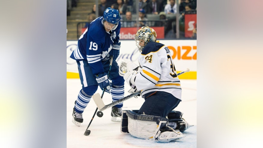 Toronto Maple Leafs' Joffrey Lupul (19) battles for the puck with Buffalo Sabres goaltender Michal Neuvirth during the second period of an NHL hockey game, Tuesday, Oct. 28, 2014 in Toronto. (AP Photo/The Canadian Press, Frank Gunn)