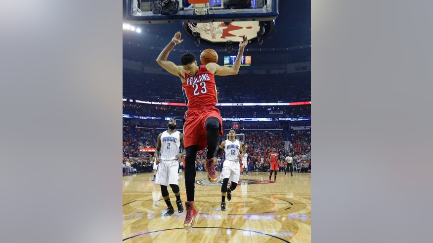 New Orleans Pelicans forward Anthony Davis (23) slam dunks in front of Orlando Magic forward Kyle O'Quinn (2) and forward Tobias Harris (12) in the first half of an NBA basketball game in New Orleans, Tuesday, Oct. 28, 2014. (AP Photo/Gerald Herbert)