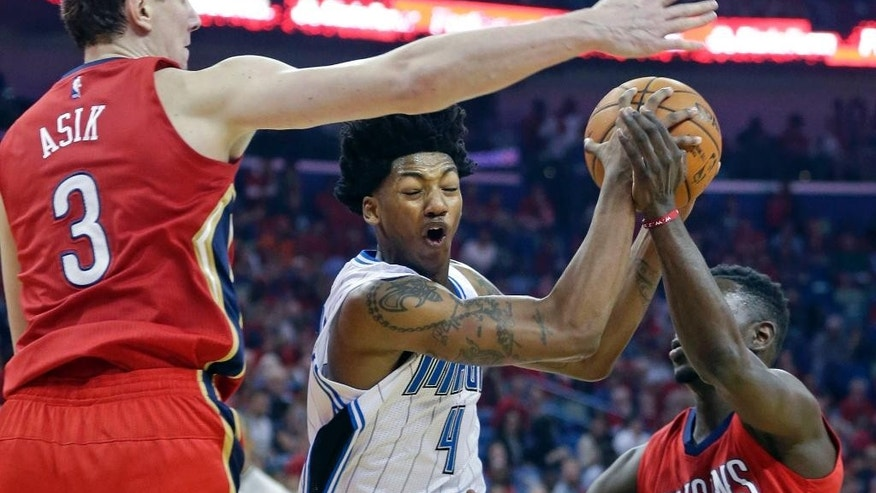 Orlando Magic guard Elfrid Payton (4) drives to the basket between New Orleans Pelicans center Omer Asik (3) and guard Jrue Holiday (11) in the first half of an NBA basketball game in New Orleans, Tuesday, Oct. 28, 2014. (AP Photo/Gerald Herbert)
