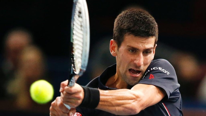 Serbia's Novak Djokovic returns the ball to German Philipp Kohlschreiber during their first round match at the ATP World Tour Masters tennis tournament at Bercy stadium in Paris, France, Tuesday, Oct. 28, 2014. Djokovic won 6-3, 6-4. (AP Photo/Michel Euler)