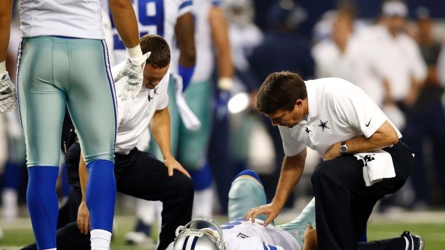 Dallas Cowboys' Tony Romo (9) is looked at by team staff after being sacked by Washington Redskins' Keenan Robinson during the second half of an NFL football game, Monday, Oct. 27, 2014, in Arlington, Texas. Romo was injured on the play. (AP Photo/Tim Sharp)