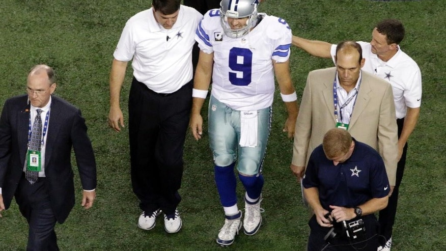 Dallas Cowboys' Tony Romo (9) is helped off the field by team medical staff and head coach Jason Garrett, bottom right, after being injured during the second half of an NFL football game against the Washington Redskins, Monday, Oct. 27, 2014, in Arlington, Texas. Romo was injured when he was sacked by Washington Redskins' Keenan Robinson. (AP Photo/Roger Steinman)