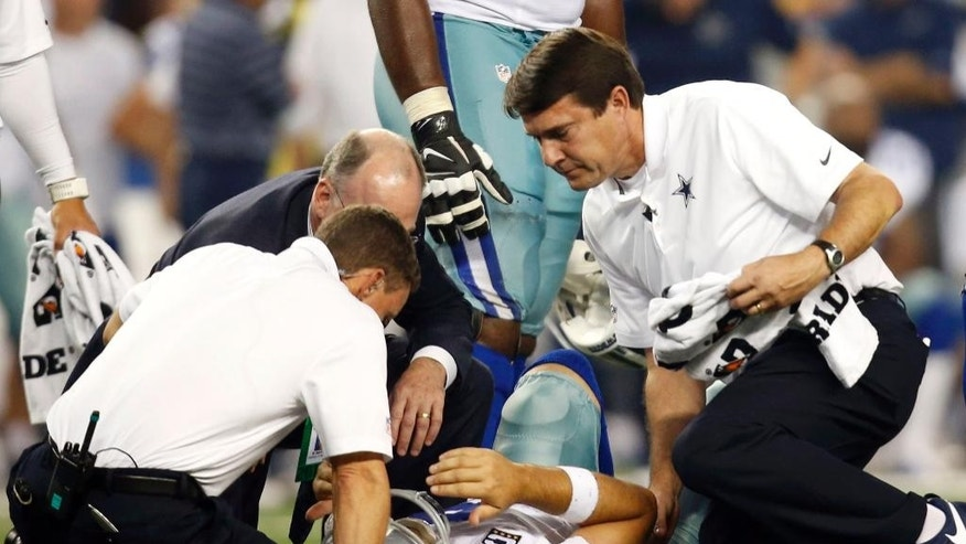 Dallas Cowboys' Tony Romo (9) is looked at by team medical staff after he was sacked by Washington Redskins' Keenan Robinson during the second half of an NFL football game, Monday, Oct. 27, 2014, in Arlington, Texas. Romo was injured on the sack. (AP Photo/Tim Sharp)