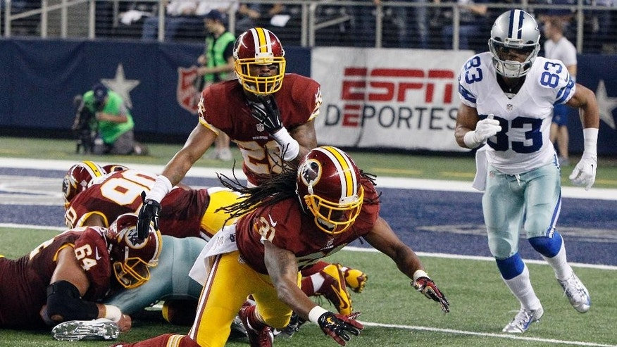 Washington Redskins strong safety Brandon Meriweather (31) leaps to recover a Dallas Cowboys' DeMarco Murray fumble as Cowboys receiver Terrance Williams (83) watches during the first half of an NFL football game, Monday, Oct. 27, 2014, in Arlington, Texas. (AP Photo/Brandon Wade)