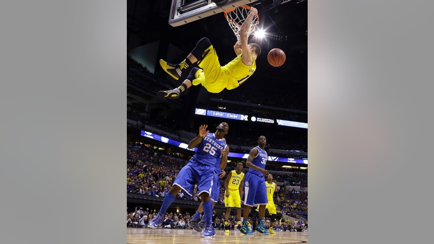 FILE - In this March 30, 2014, file photo, Michigan's Nik Stauskas, center, dunks over Kentucky's Dominique Hawkins during the second half of an NCAA Midwest Regional final college basketball tournament game in Indianapolis. Michigan has had to deal with stars leaving early for the pros for a while now, but the trio of Nik Stauskas, Glenn Robinson III and Mitch McGary may be difficult to replace. (AP Photo/Michael Conroy, File)