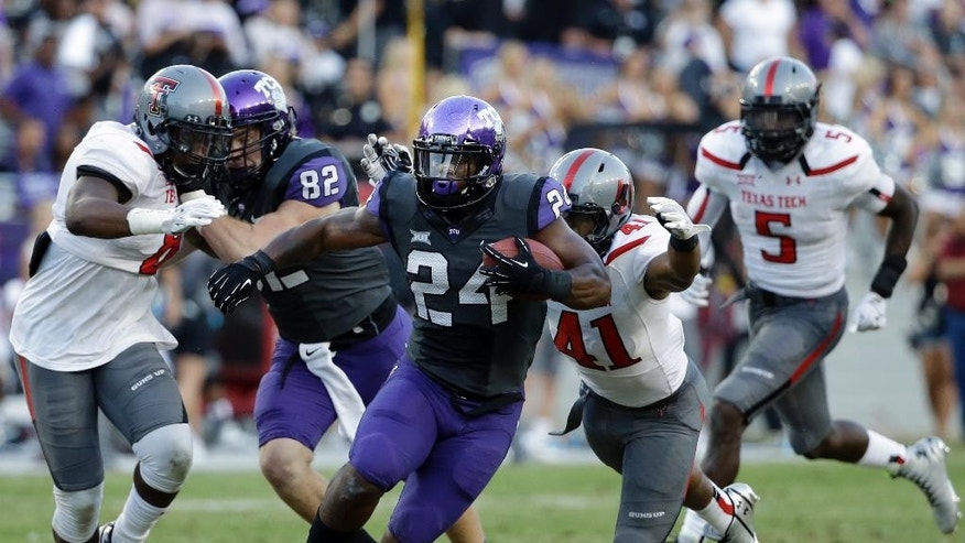TCU running back Trevorris Johnson (24) attempts to evade a tackle by Texas Tech's Malik Jenkins (41) in the second half of an NCAA college football game, Saturday, Oct. 25, 2014, in Fort Worth, Texas. TCU won 82-27. (AP Photo/Tony Gutierrez)