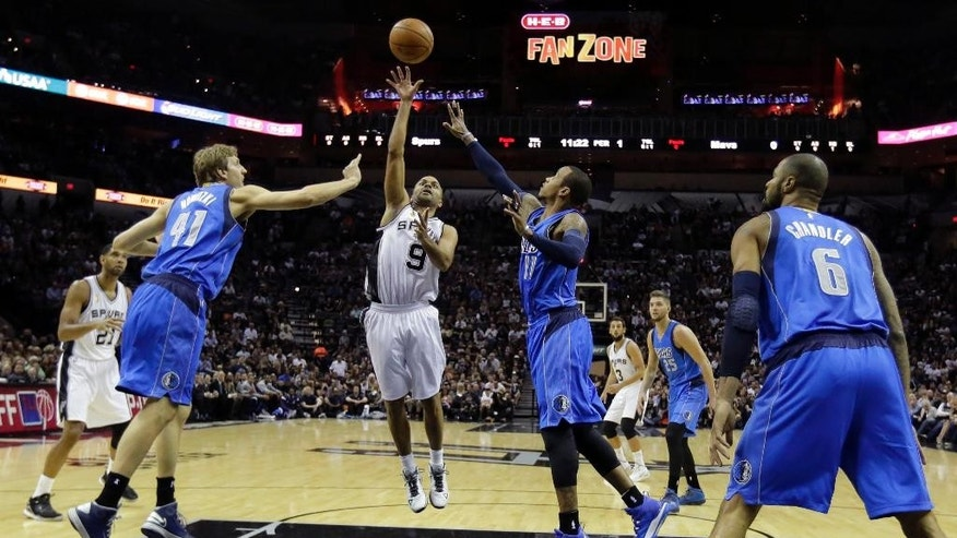 San Antonio Spurs' Tony Parker (9), of France, shoots over Dallas Mavericks' Dirk Nowitzki (41), of Germany, and Monta Ellis (11) during the first half of an NBA basketball game, Tuesday, Oct. 28, 2014, in San Antonio. (AP Photo/Eric Gay)