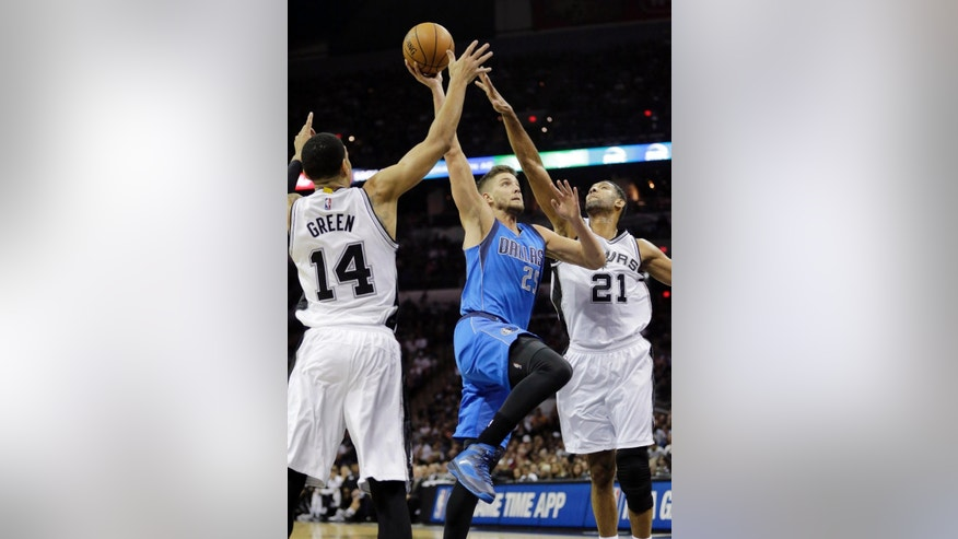 Dallas Mavericks' Chandler Parsons (25) drives between San Antonio Spurs' Danny Green (14) and Tim Duncan (21) to score during the first half of an NBA basketball game, Tuesday, Oct. 28, 2014, in San Antonio. (AP Photo/Eric Gay)