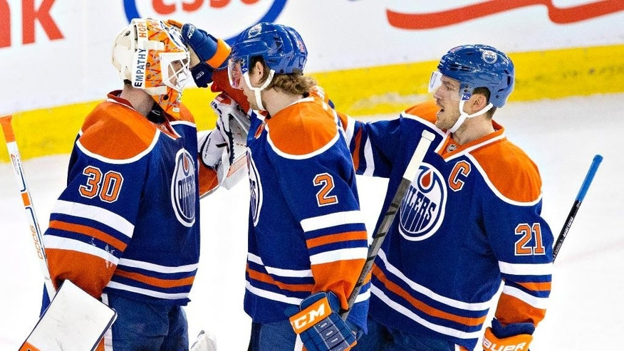 Edmonton Oilers goalie Ben Scrivens (30), Jeff Petry (2) and Andrew Ference (21) celebrate the win over the Montreal Canadiens during NHL hockey action in Edmonton, Alberta, on Monday, Oct. 27, 2014.  (AP Photo/The Canadian Press, Jason Franson)