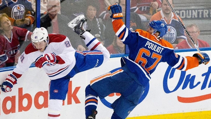 Montreal Canadiens Lars Eller (81) is checked by Edmonton Oilers Benoit Pouliot (67) during third period NHL hockey action in Edmonton, Alberta, on Monday, Oct. 27, 2014.  (AP Photo/The Canadian Press, Jason Franson)