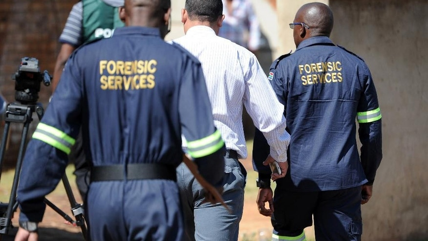 South African forensic investigators walk outside the home of actress and singer Kelly Khumalo in Vosloorus, east of Johannesburg, South Africa, Monday Oct. 27, 2014. Senzo Meyiwa, the captain of the South African national soccer team, was fatally shot at Khumalo's house during an attempted robbery Sunday night as he tried to apprehend the intruders, police and an eyewitness said. (AP Photo)