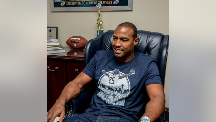 In this Sept. 1, 2014 photo provided by FanPrint, former NFL football player Darren Woodson poses for a photo in a FanPrint T-shirt in Dallas. The company provides custom-made goods to the public, most notably creative T-shirts for which consumers can choose artwork that includes offerings by graphic designers worldwide. The company has the approval of NFL Players Inc., the marketing arm of the players' union, and a portion of proceeds from sales of FanPrint merchandise goes to the Gene Upshaw Player Assistance Trust Fund to help former players in need. (AP Photo/FanPrint)