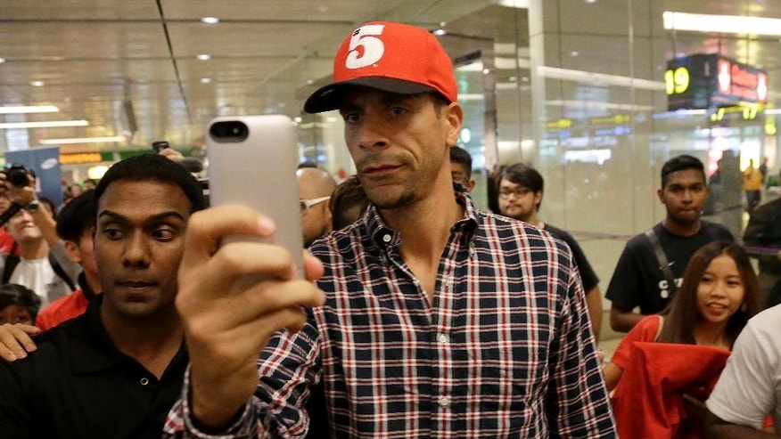 "FILE - In this Tuesday, May 13, 2014, Manchester United's Rio Ferdinand takes a ""selfie"" upon arrival at the Changi International Airport in Singapore. The English Football Association has banned Queens Park Rangers defender Rio Ferdinand for three games over a tweet containing a derogatory reference to women.  (AP Photo/Wong Maye-E, File)"