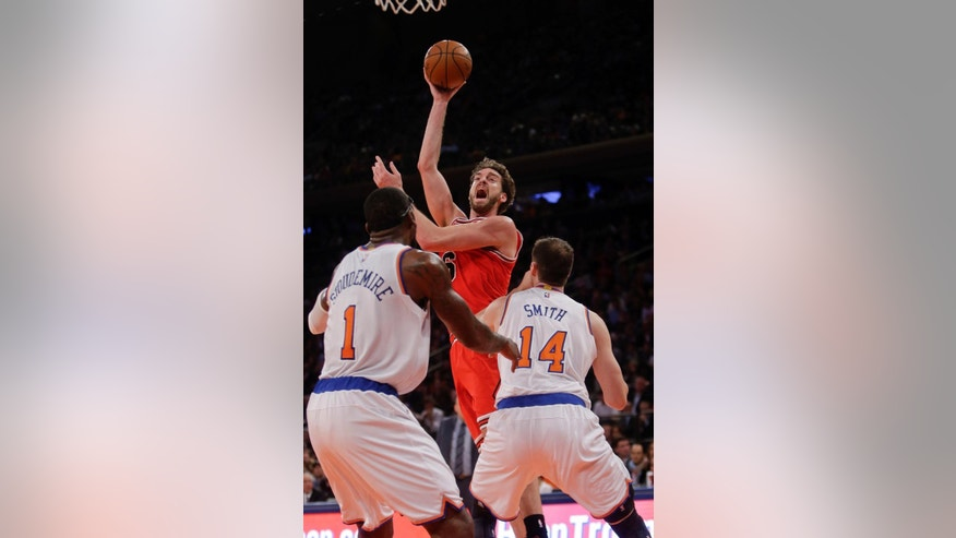 Chicago Bulls' Pau Gasol shoots over New York Knicks' Amar'e Stoudemire (1) and Jason Smith (14) during the first half of an NBA basketball game Wednesday, Oct. 29, 2014, in New York. (AP Photo/Frank Franklin II)