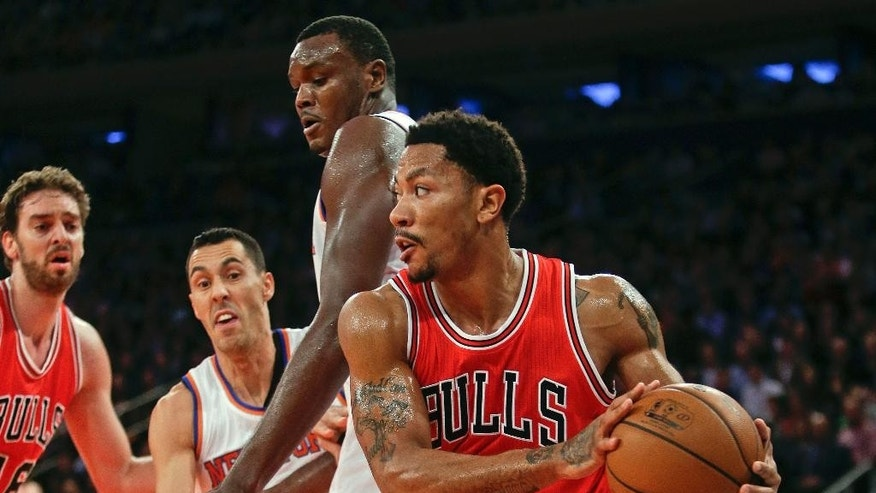 Chicago Bulls' Derrick Rose (1) looks to pass away from New York Knicks' Samuel Dalembert, center, and Pablo Prigioni, left, during the first half of an NBA basketball game Wednesday, Oct. 29, 2014, in New York. (AP Photo/Frank Franklin II)