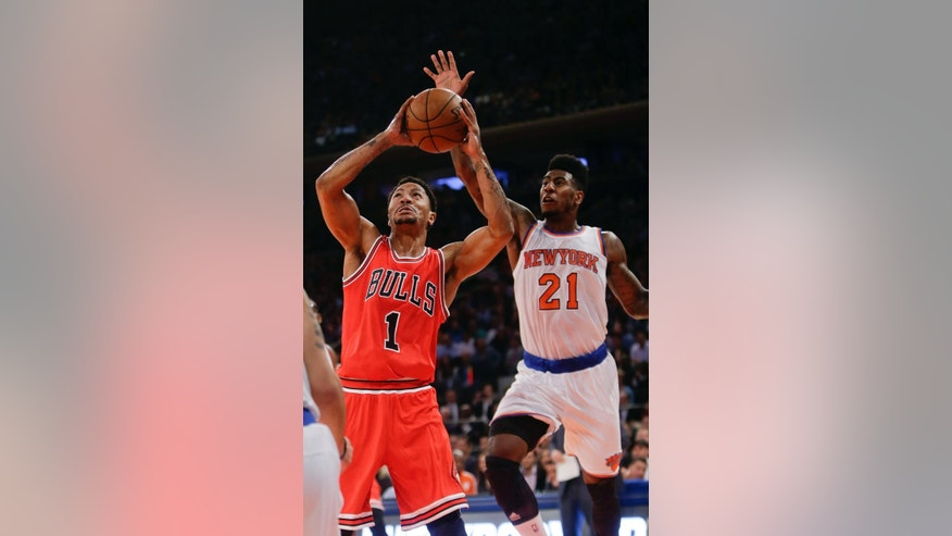 Chicago Bulls guard Derrick Rose (1) drives past New York Knicks' Iman Shumpert (21) during the first half of an NBA basketball game Wednesday, Oct. 29, 2014, in New York. (AP Photo/Frank Franklin II)
