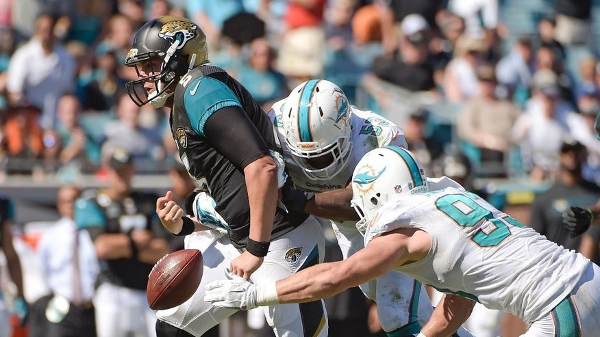 Jacksonville Jaguars quarterback Blake Bortles, left, fumbles the ball as he is hit by Miami Dolphins middle linebacker Jason Trusnik, right, and linebacker John Lotulelei, center, during the first half of an NFL football game in Jacksonville, Fla., Sunday, Oct. 26, 2014. (AP Photo/Phelan M. Ebenhack)