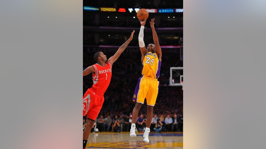 Los Angeles Lakers guard Kobe Bryant, right, puts up a shot as Houston Rockets guard Trevor Ariza defends during the first half of an NBA basketball game, Tuesday, Oct. 28, 2014, in Los Angeles. (AP Photo/Mark J. Terrill)