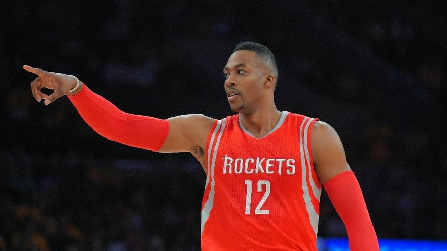 Houston Rockets center Dwight Howard gestures toward the Los Angeles Lakers bench prior to an NBA basketball game, Tuesday, Oct. 28, 2014, in Los Angeles. (AP Photo/Mark J. Terrill)