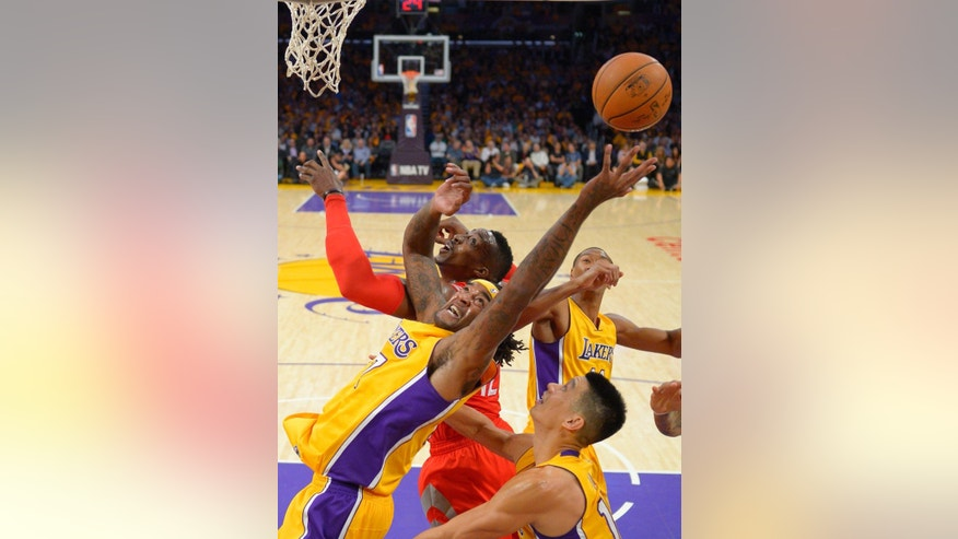 Los Angeles Lakers forward Jordan Hill, left, and Houston Rockets center Dwight Howard, top, battle for a rebound along with guard Jeremy Lin, lower right, and forward Wesley Johnson during the first half of an NBA basketball game, Tuesday, Oct. 28, 2014, in Los Angeles. (AP Photo/Mark J. Terrill)