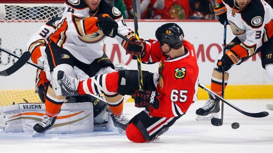 Anaheim Ducks defenseman Cam Fowler (4) pushes down Chicago Blackhawks center Andrew Shaw (65) during the first period of an NHL hockey game Tuesday, Oct. 28, 2014, in Chicago.  (AP Photo/Jeff Haynes)