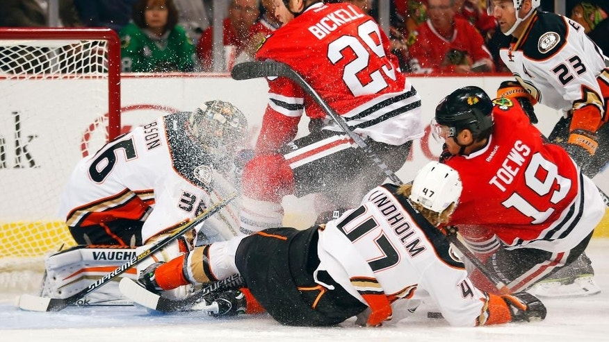 Chicago Blackhawks left wing Bryan Bickell (29) and center Jonathan Toews (19) run into Anaheim Ducks goalie John Gibson (36) and defenseman Hampus Lindholm (47) during the first period of an NHL hockey game Tuesday, Oct. 28, 2014, in Chicago.  (AP Photo/Jeff Haynes)