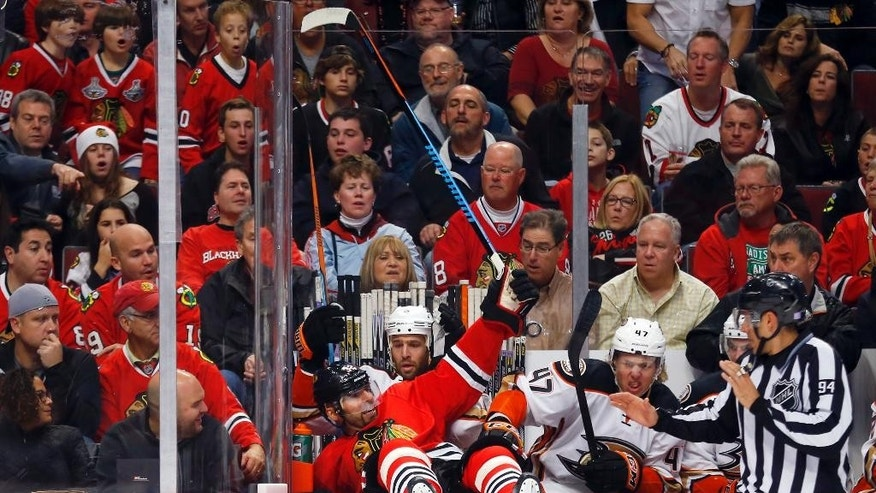 Chicago Blackhawks defenseman Michal Rozsival is checked into the Anaheim Ducks bench during the first period of an NHL hockey game Tuesday, Oct. 28, 2014, in Chicago.  (AP Photo/Jeff Haynes)