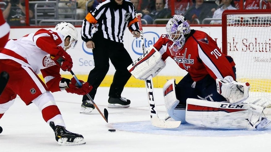 Detroit Red Wings center Gustav Nyquist (14), from Sweden, works the puck before scoring a goal past Washington Capitals goalie Braden Holtby (70) in the second period of an NHL hockey game, Wednesday, Oct. 29, 2014, in Washington. (AP Photo/Alex Brandon)