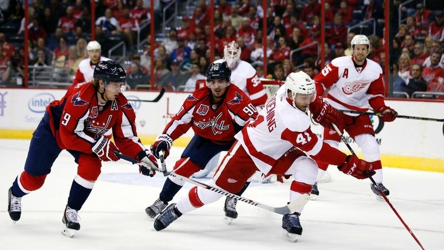 Detroit Red Wings right wing Luke Glendening (41) works to control the puck as he is pursued by Washington Capitals center Nicklas Backstrom (19), from Sweden, and left wing Marcus Johansson (90), from Sweden, in the first period of an NHL hockey game, Wednesday, Oct. 29, 2014, in Washington. (AP Photo/Alex Brandon)