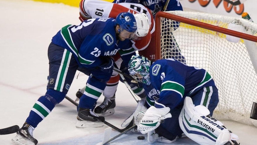 Vancouver Canucks' goalie Ryan Miller, right, covers up the puck as Alexander Edler, left, of Sweden, checks Carolina Hurricanes' Jiri Tlusty, of the Czech Republic, during the third period of an NHL hockey game, Tuesday, Oct. 28, 2014 in Vancouver, British Columbia. (AP Photo/The Canadian Press, Darryl Dyck)