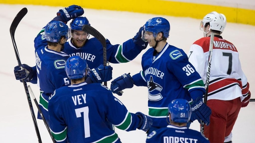 Vancouver Canucks' Luca Sbisa, of Switzerland (5), Yannick Weber, of Switzerland (6), Jannik Hansen, of Denmark (36), Linden Vey (7) and Derek Dorsett (51) celebrate Hansen's goal as Carolina Hurricanes' Ryan Murphy, far right, skates to the bench during the second period of an NHL hockey game, Tuesday, Oct. 28, 2014 in Vancouver, British Columbia. (AP Photo/The Canadian Press, Darryl Dyck)