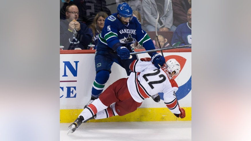 Vancouver Canucks' Luca Sbisa, of Switzerland, (5) checks Carolina Hurricanes' Zach Boychuk during the second period of an NHL hockey game, Tuesday, Oct. 28, 2014 in Vancouver, British Columbia. (AP Photo/The Canadian Press, Darryl Dyck)